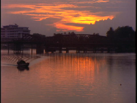 A fishing boat travels through a harbor during golden hour Stock Video Footage