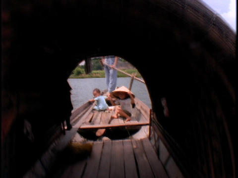 A Vietnamese woman rows a fishing boat on a river Stock Video Footage