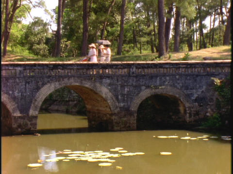 Four people cross a bridge in Hue, Vietnam Stock Video Footage