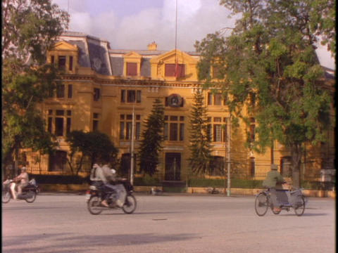 Bicycle traffic moves past a government building in Hanoi Footage