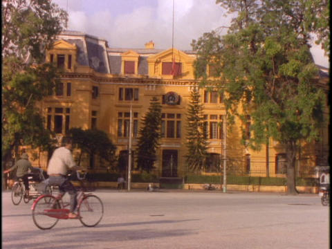 Bicycle traffic moves past a government building in Hanoi Stock Video Footage