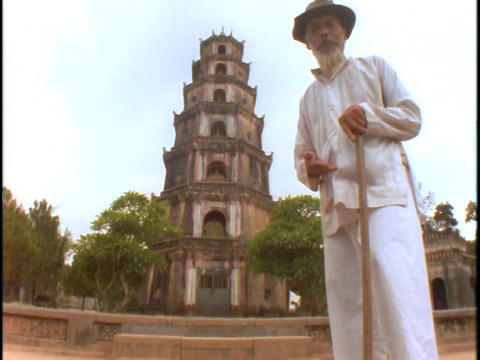 A man stands in front of a Vietnamese Buddhist temple Live Action