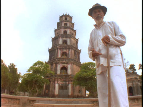A man stands in front of a Vietnamese Buddhist temple Stock Video Footage