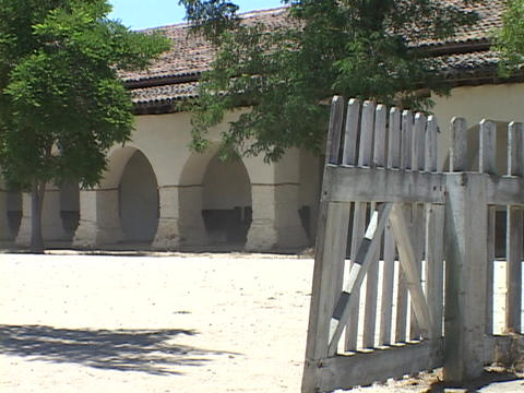 A gate swings in the wind at an old Catholic mission Footage