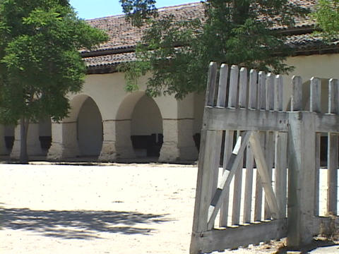 A gate swings in the wind at an old Catholic mission Stock Video Footage