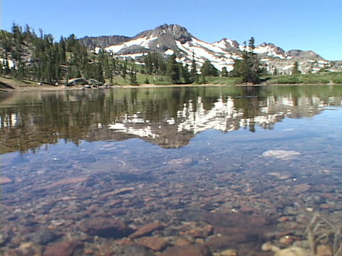 Mountains and trees reflect in a clear, calm lake Footage