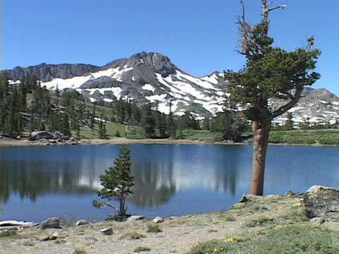 A mountain lake reflects a surrounding mountain and trees Footage