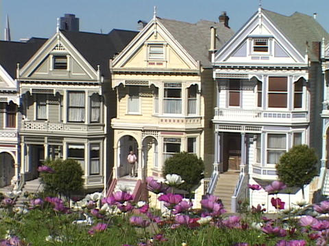Flowers wave in the breeze near a row of Victorian style... Stock Video Footage