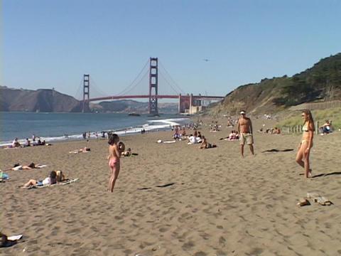 Girls play on a California beach near the Golden Gate Bridge Stock Video Footage
