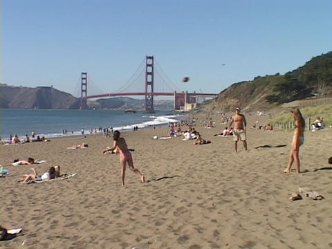 Girls play on a California beach near the Golden Gate Bridge Stock Video Footage