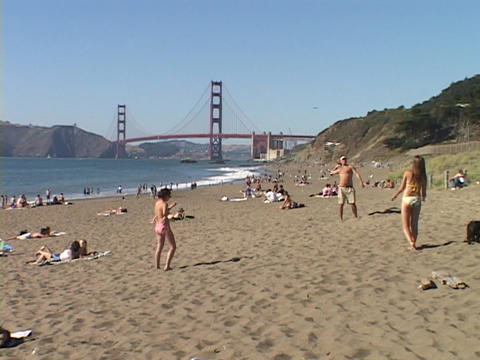 Girls play on a California beach near the Golden Gate Bridge Footage