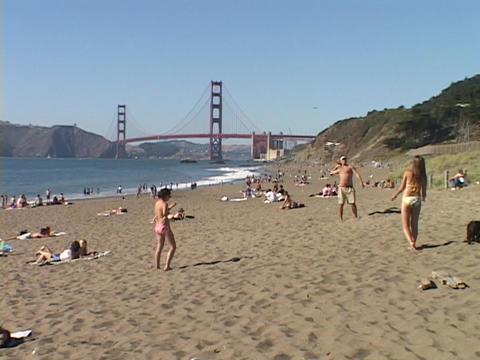 Girls play on a California beach near the Golden Gate Bridge Footage
