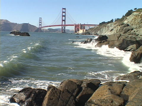 Waves crash on the shore near the Golden Gate Bridge Footage