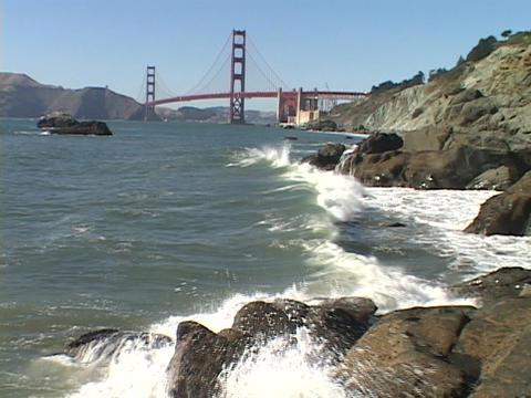 Waves crash on the shore near the Golden Gate Bridge Stock Video Footage