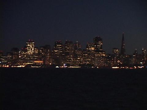 San Francisco lights glow across a bay Stock Video Footage