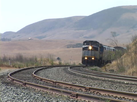 The Amtrak passenger train travels along a track Footage