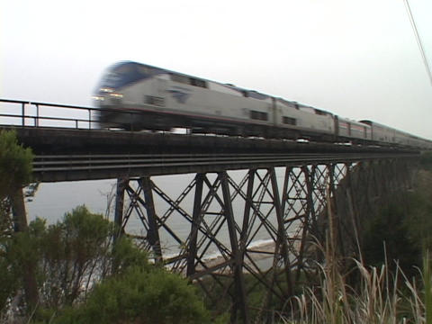 An Amtrak passenger train speeds across a high trestle Stock Video Footage