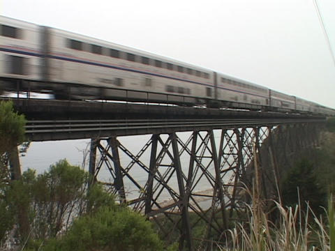 An Amtrak passenger train speeds across a high trestle Footage