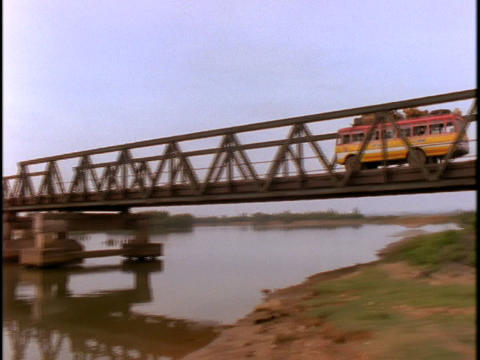 An old bus crosses a bridge which used to be the border between North and South Vietnam Footage