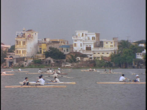 Boaters row across a large lake in central Hanoi, Vietnam Stock Video Footage