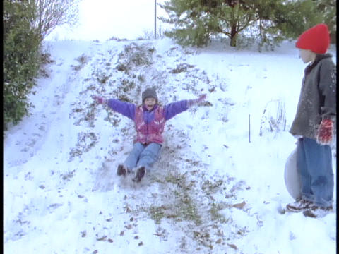 Children slide down a hill Footage