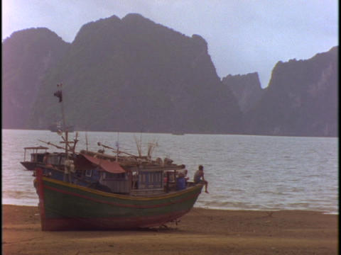 A Vietnamese fishing boat sits in dry-dock on a beach at low tide Footage