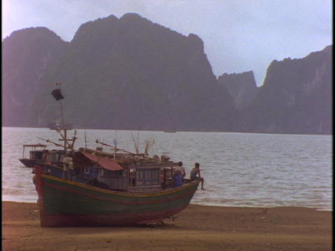 A Vietnamese fishing boat sits in dry-dock on a beach at... Stock Video Footage
