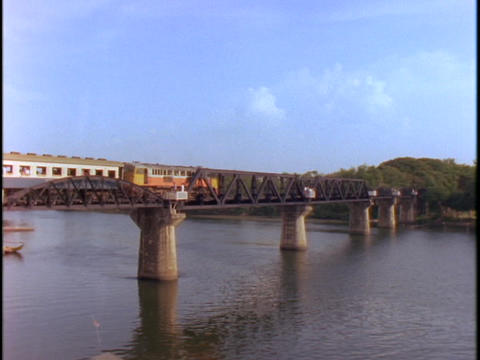 An old-fashioned Asian passenger train crosses the bridge at the river Kwai Footage