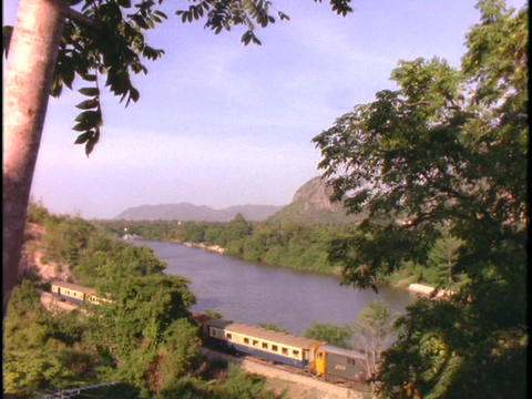 An Asian passenger train travels through a jungle in Thailand Footage