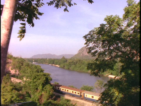 An Asian passenger train travels through a jungle in... Stock Video Footage