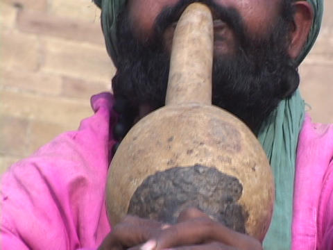 A snake charmer plays music for a cobra snake in India Footage