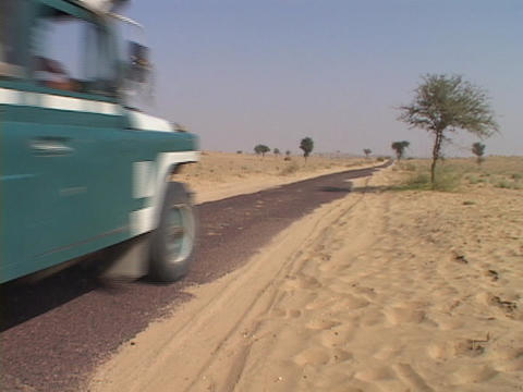 An overcrowded bus drives through the desert on narrow road Stock Video Footage
