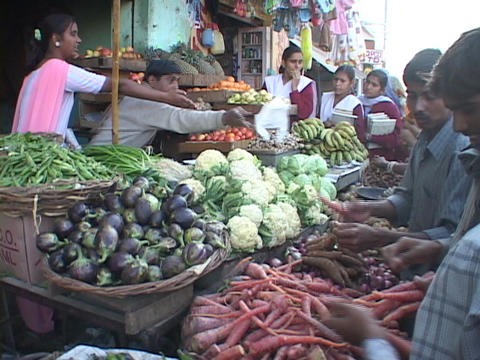 A street vendor sells vegetables at a market in India Stock Video Footage