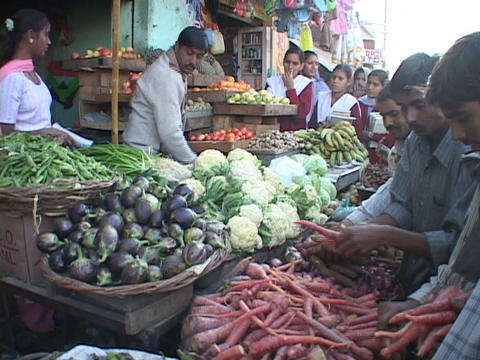 A street vendor sells vegetables at a market in India Footage