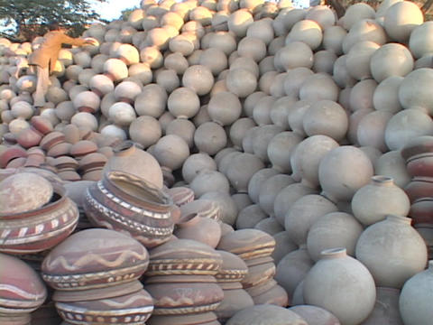 A man stacks pots in an enormous pile of pottery Footage
