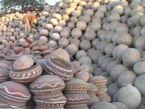 A man stacks pots in an enormous pile of pottery Stock Video Footage