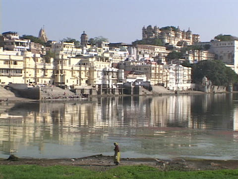 A pedestrian walks by a lake near the palaces in Udaipur, India Footage