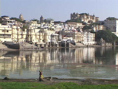 A pedestrian walks by a lake near the palaces in Udaipur,... Stock Video Footage
