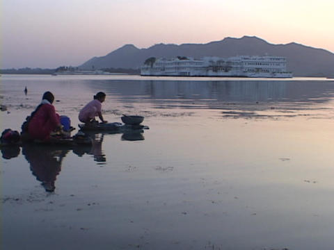 Women wash clothes in a lake Stock Video Footage