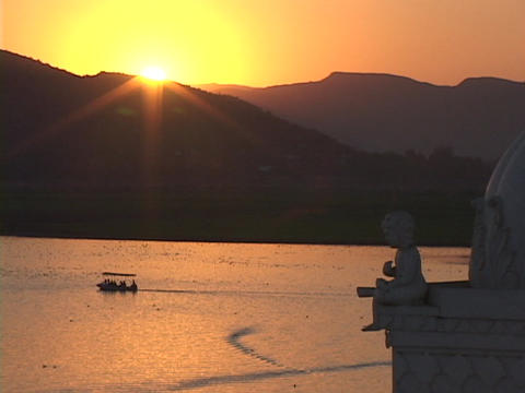 A small boat floats on a lake near a palace at golden hour Stock Video Footage