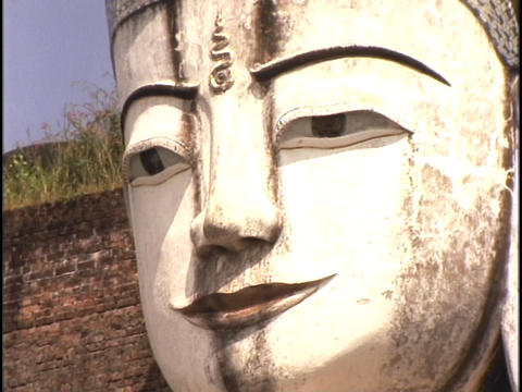 A Buddha face stares out into the distance Stock Video Footage