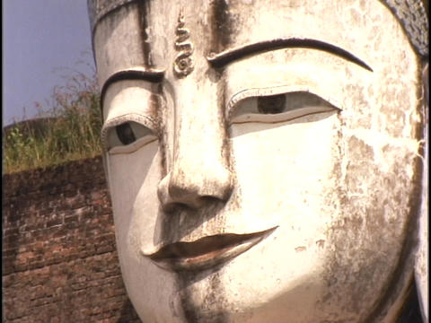 A Buddha face stares out into the distance Footage