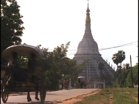 A horse cart travels in front of a giant Buddhist pagoda... Stock Video Footage