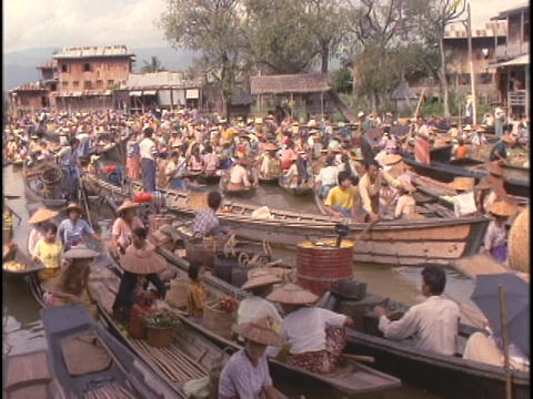 Vendors float their boats on Inle Lake at a floating market Stock Video Footage