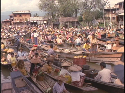 Vendors float their boats on Inle Lake at a floating market Footage