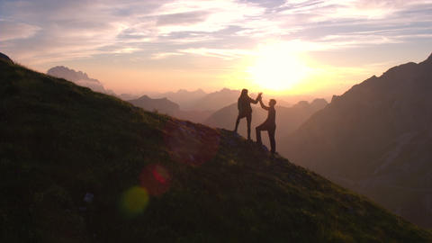Aerial - Silhouette of a couple giving each other a high five celebrating succes Footage