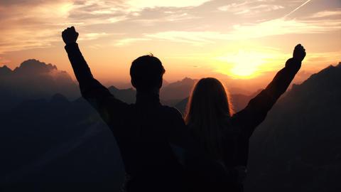 Achievement concept, edited - Embraced couple raises their arms Live Action
