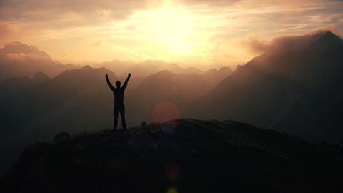 Aerial, edited - Triumphant hiker standing on top of the mountain raising arms Live Action