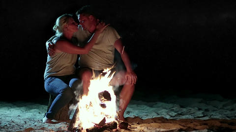 Romantic couple near fire at night while camping Footage