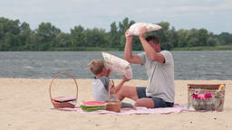 Happy family playing pillows fight on beach Footage